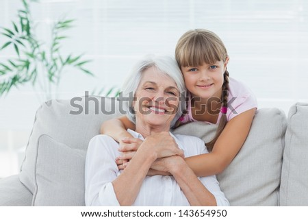 Little girl hugging her grandmother sitting on the couch - stock photo