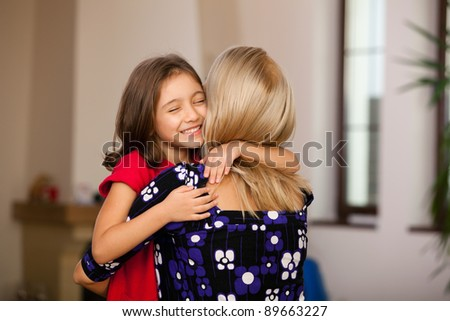 little girl hugging her mother at home