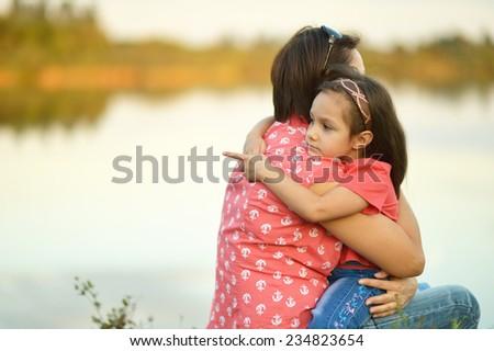 Little girl hugging her mother near the lake,girl poing her finger at something - stock photo