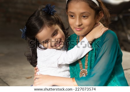 little girl hugging her sister - stock photo