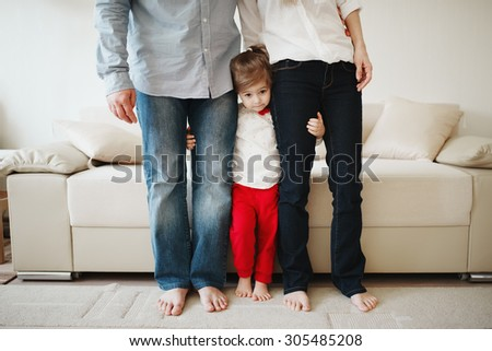 little girl hugging mom and dad for legs - stock photo