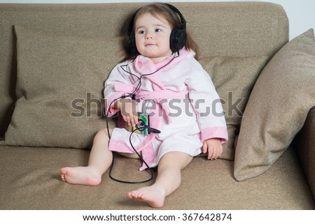 little girl in a bathrobe on the couch with earphones and listening music from smartphone