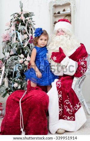 little girl in a beautiful blue dress sits on a lap at Saint Nicolas about a New Year tree