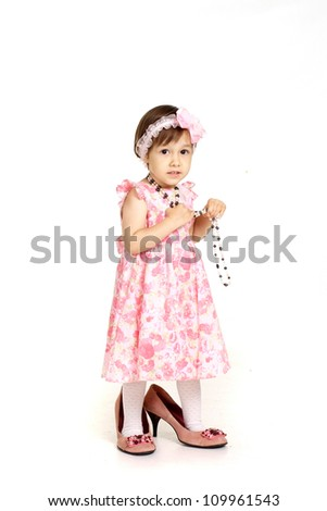 Little girl in a beautiful dress and big shoes