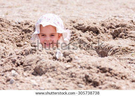 little girl in a big hat hidden in a hole on the beach with only her head sticking out - stock photo