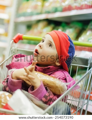 Little girl in a big store with products in the cart. - stock photo