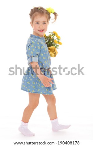 Little girl in a blue dress goes with a bouquet of flowers