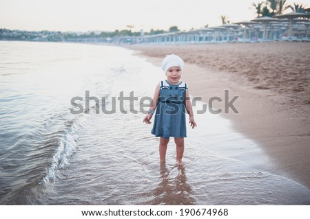 Little girl in a blue dress on the beach