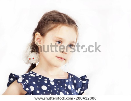 Little girl in a blue polka-dot dress with pigtails - stock photo