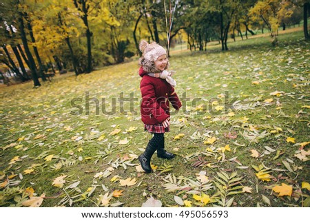 Little girl in a bright autumn park