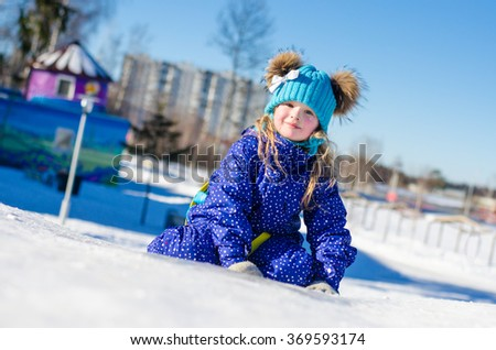 Little girl in a bright blue winter clothes sitting in the snow in sunny cold winter day. - stock photo