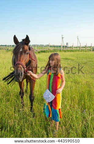 Little girl in a bright dress and go with the horse on the meadow