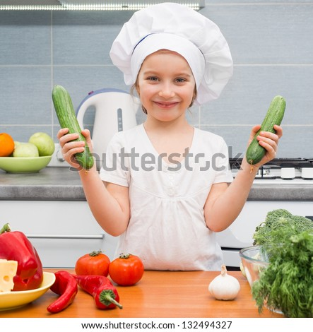 little girl in a cap chef in the kitchen with cucumbers