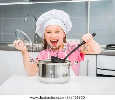 little girl in a cap chef prepares soup - stock photo