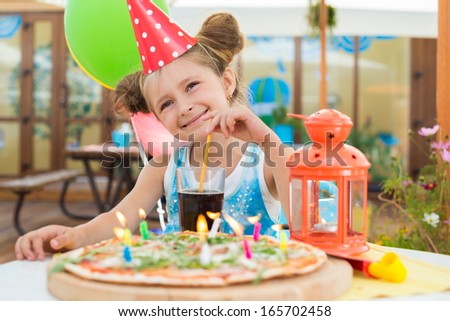 Little girl in a celebratory cap in a cafe with a pizza and a drink - stock photo