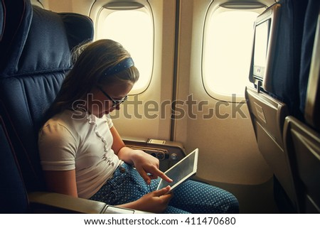 little girl in a chair on board an airplane with tablet computer