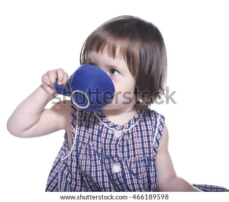 little girl in a checkered dress drinks from a mug isolated on white background