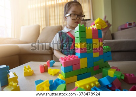 little girl in a colorful shirt playing with construction toy blocks building a tower . Kids playing. Children at day care. Child and toys. - stock photo