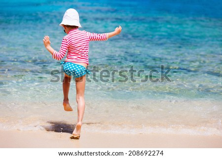 Little girl in a colorful sun protection swimwear on vacation splashing in a shallow water at tropical beach - stock photo