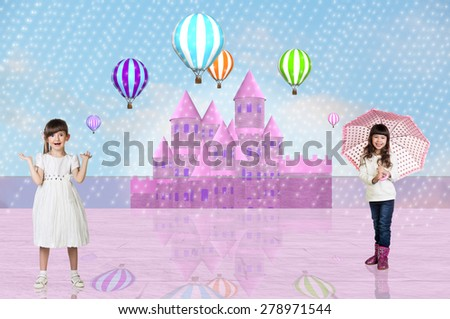 Little girl in a dress and another one with an umbrella in front of a pink fairy castle  - stock photo