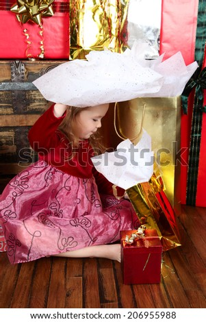 Little girl in a dress opening christmas gifts - stock photo