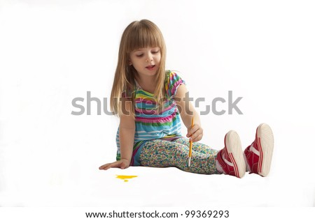 little girl in a dress the color paints paints sitting on the floor