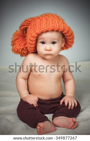 Little girl in a funny hat on a gray background