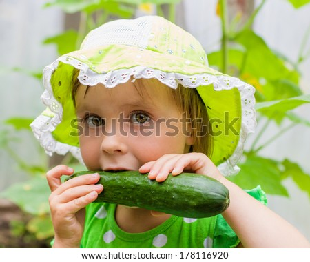 Little girl in a green hat, eating fresh cucumber from the garden - stock photo