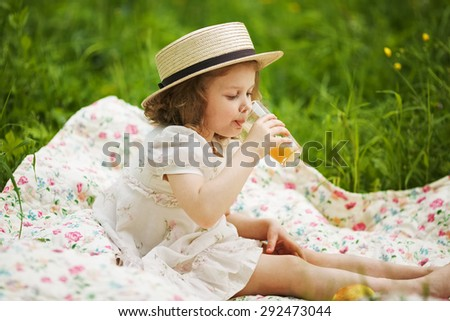 Little girl in a hat drinking orange juice - stock photo