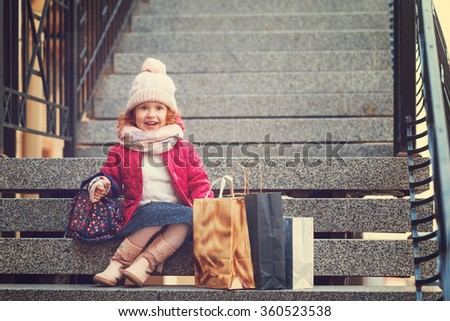 Little girl in a hat, jacket and scarf holding colorful shopping bags. Child in a shop buying clothes. - stock photo