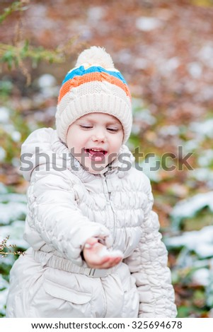 little girl in a hat with a scarf and a light jacket walking on the street in the autumn when he fell on his first showing palms