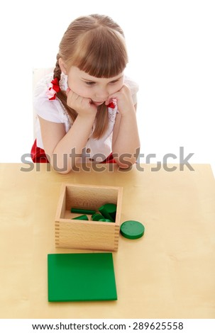 Little girl in a Montessori kindergarten studying the material - isolated on white background - stock photo