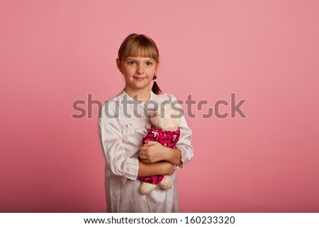 Little girl in a nightgown with a teddy bear on a pink background - stock photo