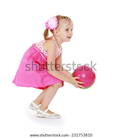 Little girl in a pink dress catches the ball. Isolated on white background . - stock photo