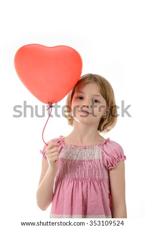 Little girl in a pink dress holding a red balloon in the shape of a heart on a white background