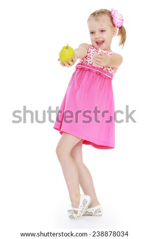 Little girl in a pink dress holds out a green apple photo in full growth. Isolated on white background studio photo.