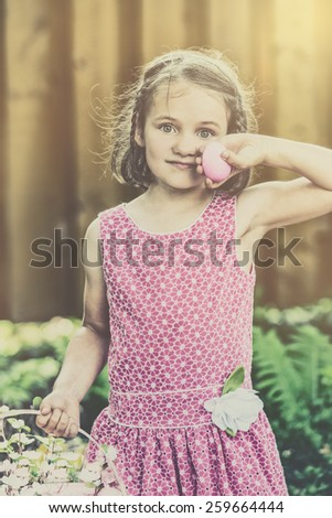 Little girl in a pink dress poses with a smile holding a color dyed egg she found during an Easter egg hunt outside during the spring season.  Part of a series.  Filtered for a retro, vintage look. - stock photo