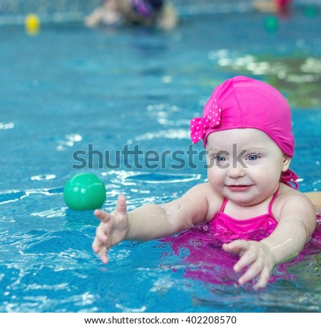 little girl in a pink swimsuit in the pool - stock photo
