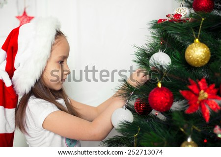 little girl in a red cap hangs on the Christmas tree new year toys