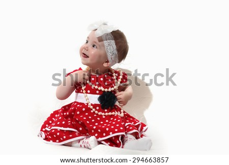 little girl in a red dress and beads