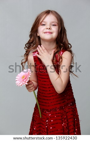 little girl in a red dress holding a fresh gerbera on a white background on Holiday