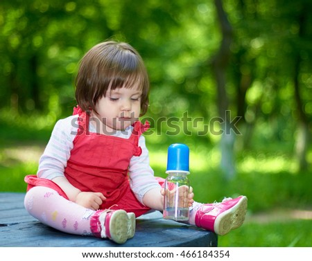 Little girl in a red dress in the nature. Keep a bottle in hand