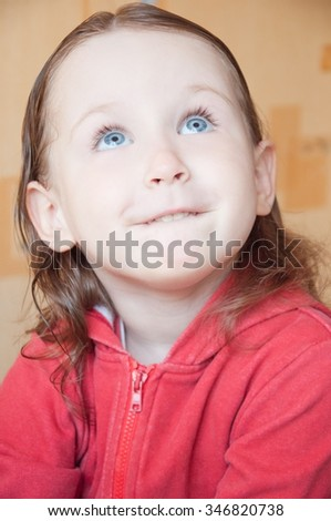 little girl in a red jacket looks upwards