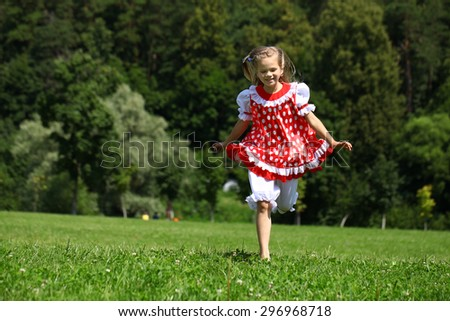 Little girl in a red polka-dot sundress into a major run on green field - stock photo