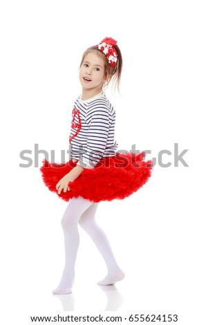 Little girl in a red skirt and bow on her head.Isolated on white background.