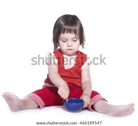 Little girl in a red suit. Holding in hands a cup and spoon. Isolated on white background.