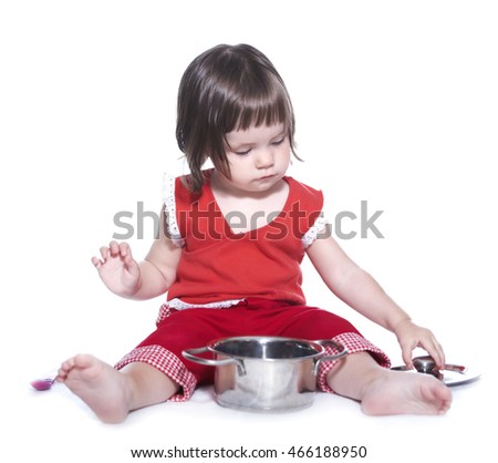 Little girl in a red suit. Playing with a saucepan and a spoon. Isolated on white background