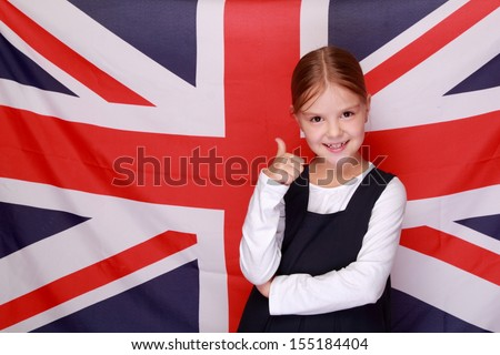 little girl in a school uniform stands on a background of the flag of Great Britain/British school girl on background of the flag of England - stock photo