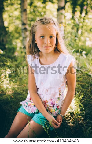 Little girl in a shirt and shorts in nature