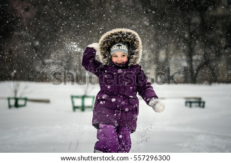 Little girl in a ski suit playing snowballs. She's going to throw a snowball. The girl is smiling and she is very fun.